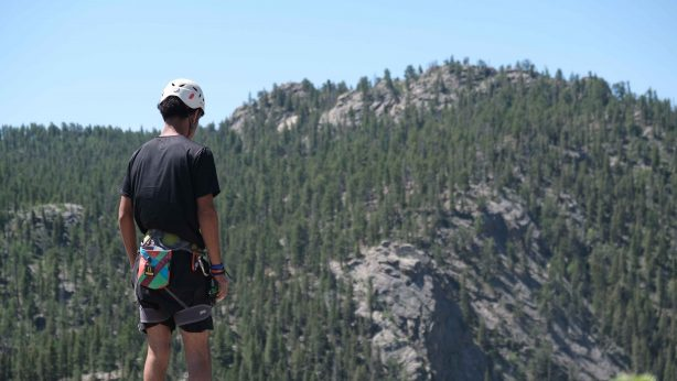 Youth in mountain climbing gear standing on top of a mountain overlooking another mountain